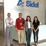 People in front of the Sidel Logo