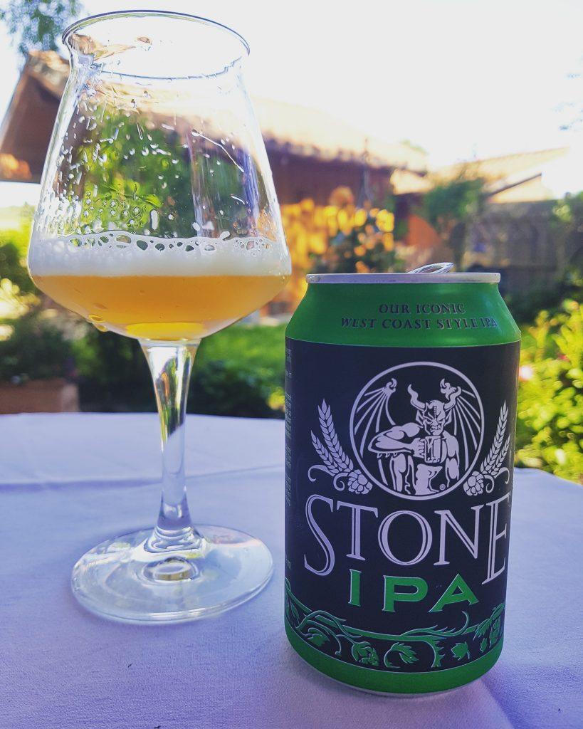 eine Dose Indian Pale Ale neben einem Glas auf einem Tisch in einem Garten