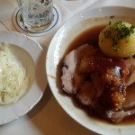 a plate with a dumpling and roast pork next to a plate with Sauerkraut