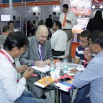 some men sitting on a table and working at the drinktec India