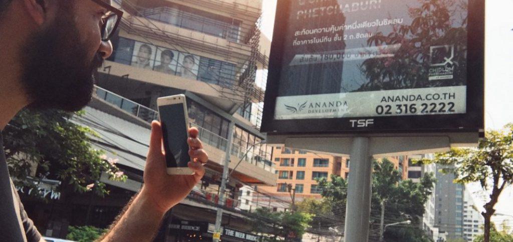 ein Mann steht mit seinem Smartphone vor einer Werbetafel