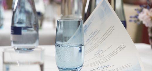 ein Glas Mineralwasser auf einer Mineralwasserkarte auf einem Tisch