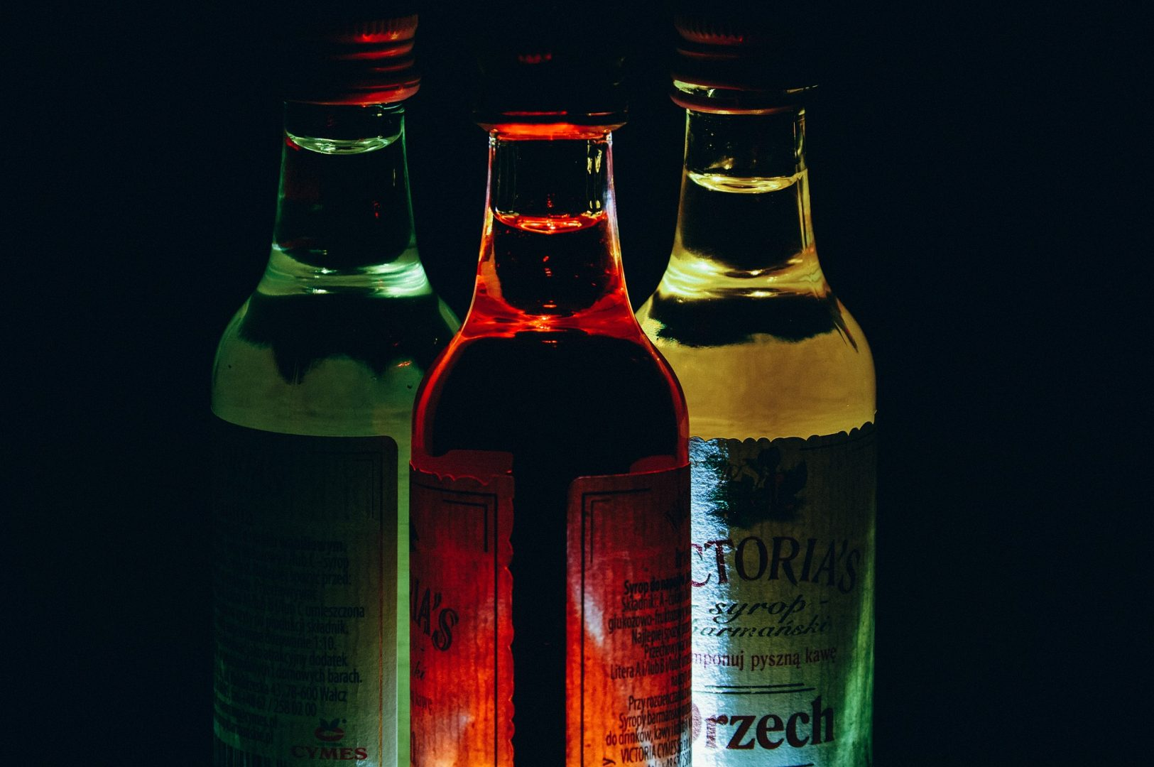 Thee illuminated bottles on a dark background