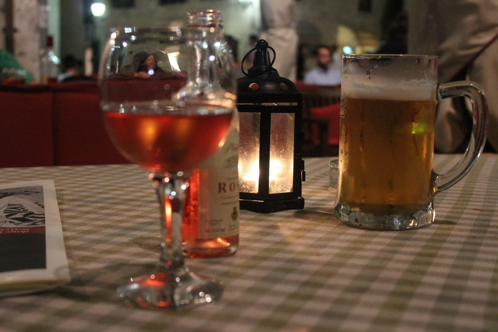 A table with a glas of wine and a beer on it