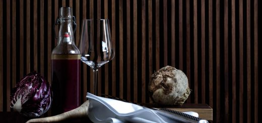 A wine glas and a bottle on a table
