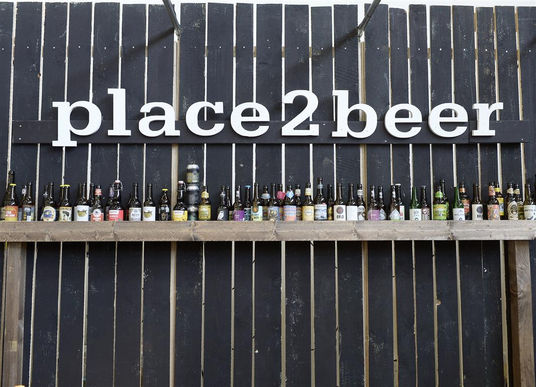 Eine Reihe voll Bier mit Place To Beer drübergeschrieben