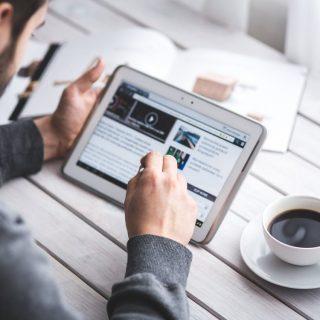 Ein Mann an seinem iPad mit einem Kaffee neben sich