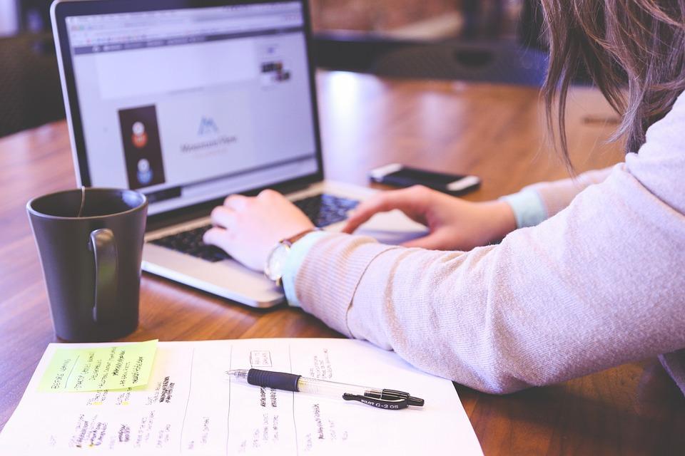 Eine Frau, die an einem Tisch mit Laptop, Kaffee, Handy und Notizbuch sitzt