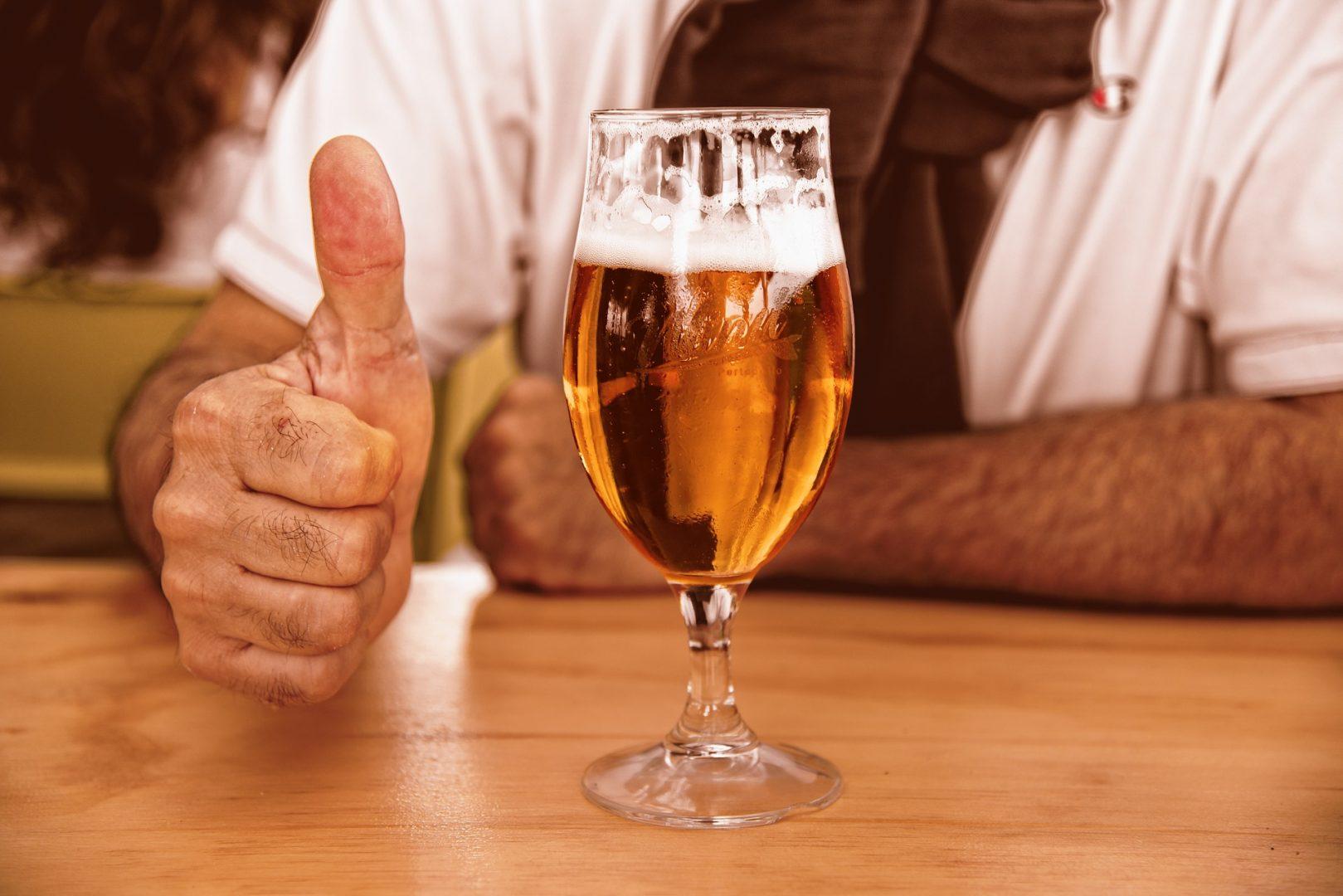 """Ein Bier und eine hand, die """"Daumen hoch"""" zeigt"""