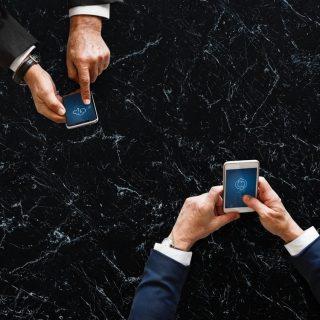 Zwei Paar Hände, die ein Smartphone halten
