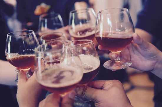 People toasting with beer in glasses
